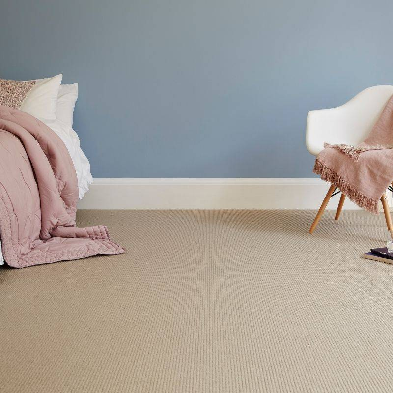 brown carpet in bedroom with chair