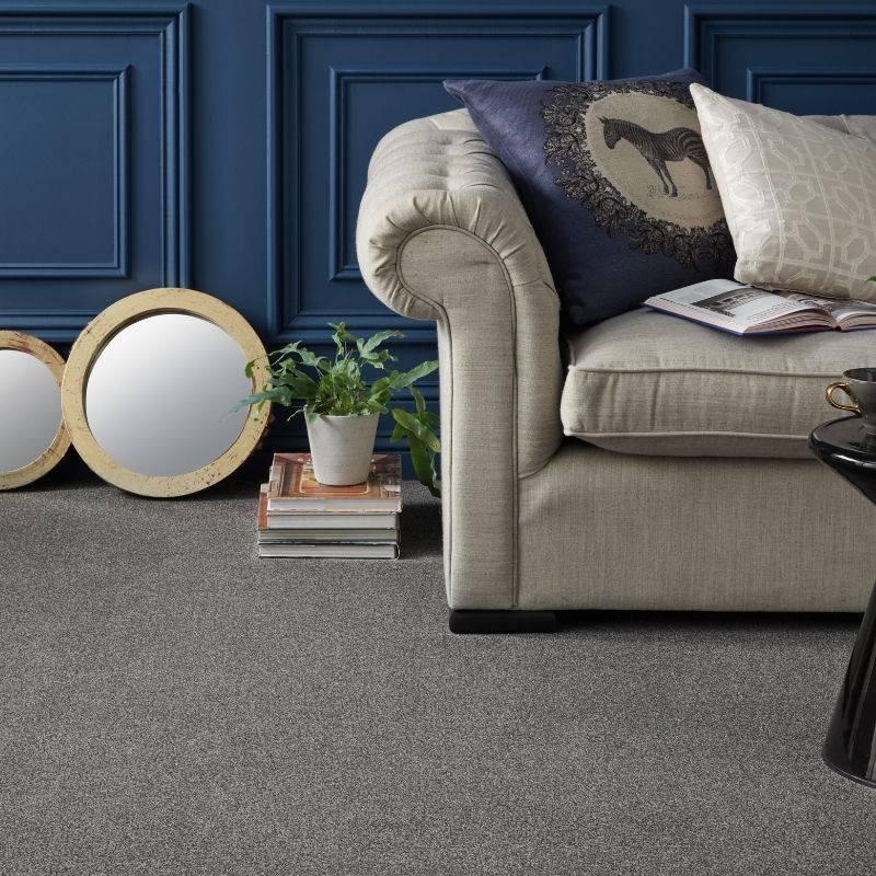 grey carpet in bedroom next to sofa