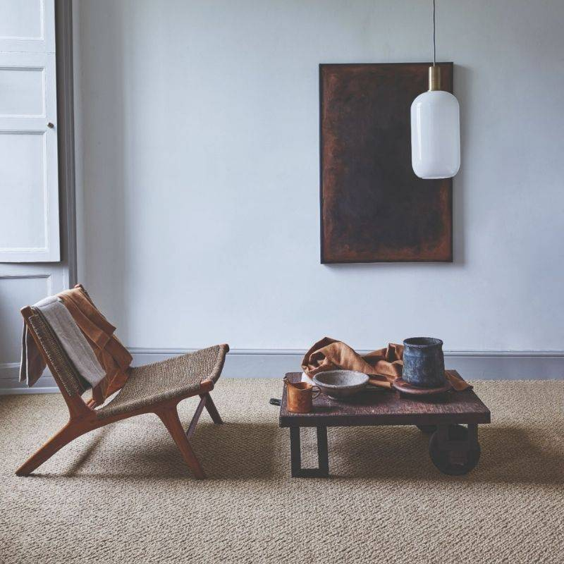 brown patterned carpet next to chair, table and artwork